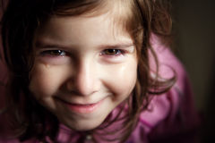 Smiling Through the Tears. A young girl with red, teary eyes looks up at the camera with a wide, closed mouth smile. It is lit from the side with very contrasty Royalty Free Stock Images