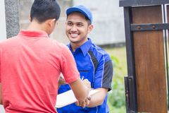 Techinician coming to customer house. Smiling techinician in blue uniform coming to customer house Royalty Free Stock Images