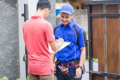 Techinician coming to customer house. Smiling techinician in blue uniform coming to customer house Stock Photography