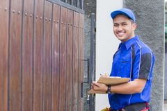 Techinician coming to customer house. Smiling techinician in blue uniform coming to customer house Royalty Free Stock Image
