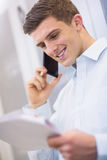 Smiling technician calling and reading a document Royalty Free Stock Photography