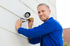 Smiling Technician Installing Camera On Wall. Smiling Young Technician Installing Camera On Wall With Screwdriver Royalty Free Stock Photos