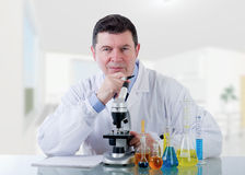 Smiling Technician  at laboratory. Smiling Technician with microscope  at laboratory Stock Photography
