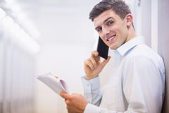 Smiling technician on the phone holding a document Royalty Free Stock Image