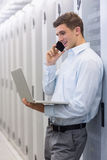 Smiling technician phoning and using his notebook Stock Photography