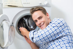 Smiling technician repairing a washing machine Royalty Free Stock Photos