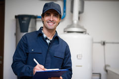 Smiling technician servicing an hot-water heater Royalty Free Stock Images