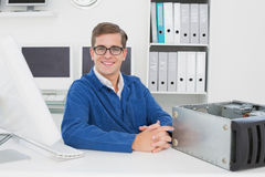 Smiling technician sitting at desk Royalty Free Stock Photography
