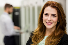 Smiling technician standing in a server room. Portrait of smiling technician standing in a server room Stock Photo