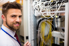 Smiling technician standing in a server room. Portrait of smiling technician standing in a server room Royalty Free Stock Image