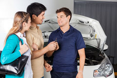 Smiling Technician Taking Car Keys From Couple Stock Photos