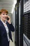 Smiling technician talking on phone while looking at server Stock Image