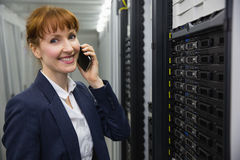 Smiling technician talking on phone while looking at server Stock Images