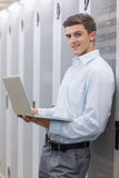 Smiling technician using his notebook. And leaning against a tower in a large data center Royalty Free Stock Photos