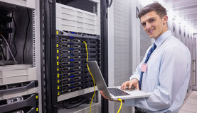 Smiling technician using laptop while analysing server Royalty Free Stock Photography