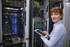 Smiling technician using tablet pc while analysing server Stock Images
