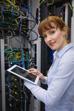 Smiling technician using tablet pc while analysing server Stock Photos