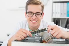 Smiling technician working on broken cpu Stock Images