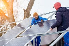 Smiling technicians mounting blue solar modules on roof of modern house as a sustainable source of alternative energy. Renewable electricity photovoltaic panel Stock Photo