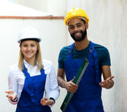 Smiling technicians smoothing the wall Stock Photography