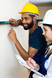 Smiling technicians smoothing the wall Royalty Free Stock Photo