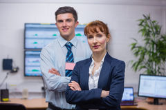 Smiling technicians standing at the camera with arms folded. In office running diagnostics in large data center Stock Photography