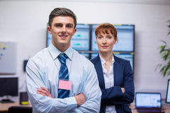 Smiling technicians standing at the camera with arms folded. In office running diagnostics in large data center Royalty Free Stock Photography