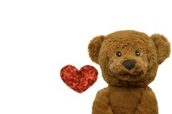 The smiling teddy bear with blurred photo of love shape. stock photo