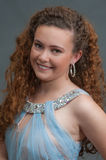 Smiling teen beauty head shot in light blue dress to left. Smiling face view of pageant girl facing left in elegant sheer dress Royalty Free Stock Photos