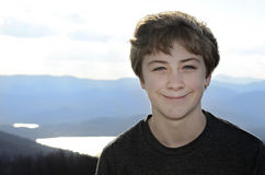 Smiling Boy. A smiling teen boy with mountains and lake in the distance royalty free stock image