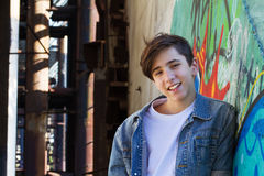 Smiling teen boy next to graffiti painted wall. Royalty Free Stock Photography