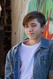 Smiling teen boy next to graffiti painted wall. Stock Photo