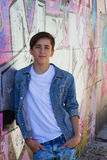 Smiling teen boy next to graffiti painted wall. Stock Image