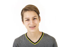 Smiling teen boy with orthodontic braces. Portrait of beautiful smiling teen boy with orthodontic braces isolated on white background. Concept of emotions Stock Image
