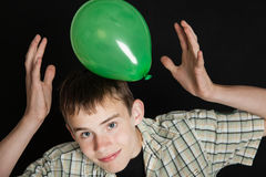Smiling Teen Boy Playing with Bright Green Balloon Stock Photo