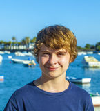 Smiling teen boy stands in front of the harbour Stock Image