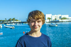 Smiling teen boy stands in front of the harbour Stock Images