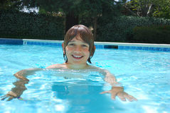 Smiling Teen Boy Swimming in Pool. Smiling teen boy swimming in the pool surrounded with white flower bushes in the background Royalty Free Stock Image