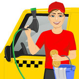 Smiling teen boy using a soapy sponge to wash a taxy car Royalty Free Stock Photo