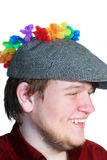 Smiling Teen Boy Wearing Flat Cap And Flowers. Profile closeup of a smiling teenage boy wearing a gray wool flat cap with a ring of colorful flowers draped on Royalty Free Stock Image