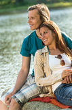 Smiling teen couple sitting on a rock Royalty Free Stock Image