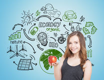 Smiling teen girl with apple, ecology icons. Portrait of a young woman wearing a black tank top, smiling and holding a red apple. She is standing near a blue Royalty Free Stock Images