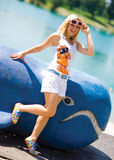 Smiling teen girl on the beach. Next to whale toy Stock Image
