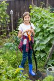Smiling teenage girl in blue rubber boots working in garden with spade. Smiling teen girl in blue rubber boots working in garden with spade Stock Images