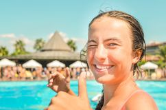 Smiling teen girl enjoing summer vacation at the hotel pool with palms and sun umbrellas on the background stock photos