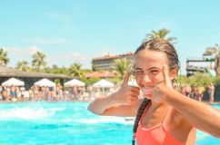 Smiling teen girl enjoing summer vacation at the hotel pool with palms and sun umbrellas on the background royalty free stock image
