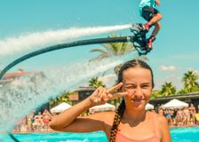 Smiling teen girl enjoing summer vacation at the pool with fly board watershow on the background stock images