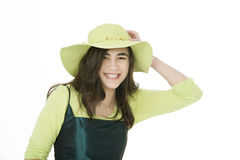 Smiling teen girl in green dress holding onto hat Stock Photography