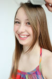 Smiling teen girl and hair brush. Teen girl having her hair brushed isolated on white Stock Photo