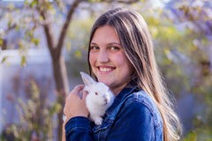 Smiling teen girl holding a baby white rabbit outdoors Royalty Free Stock Image